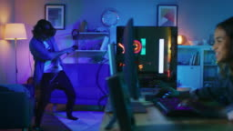 Young Man is Energetically Playing a Virtual Reality Video Game While Wearing a Headset. His Pretty Girl Friend Actively Plays an Online Shooter on a Computer in the Same Room with Neon Lights.