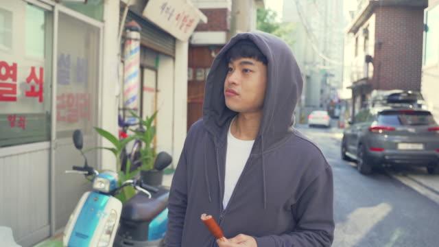 vídeos de stock e filmes b-roll de a young man (the jobless) is going around and eating a sausage on the street - cara para baixo