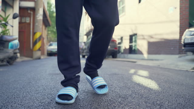 a young man (the jobless) is going around dragging his flip-flops on the street - slipper stock videos & royalty-free footage