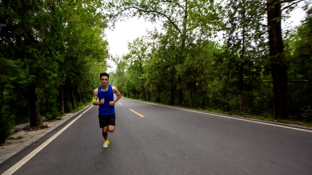 WS TS A young man is listening to music with earphones while running on a forest road