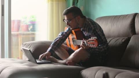 vídeos y material grabado en eventos de stock de joven está tocando la guitarra en el sofá de su casa - pasatiempos