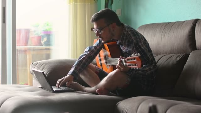 young man is playing guitar in the couch of his house - guitar stock videos & royalty-free footage