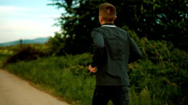 若い男が実行されています。 - 人の背中点の映像素材/bロール