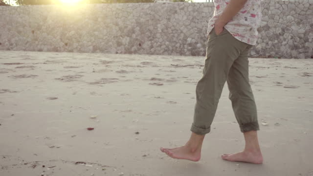 young man is walking along the sea shore enjoying the sun rays - scalzo video stock e b–roll