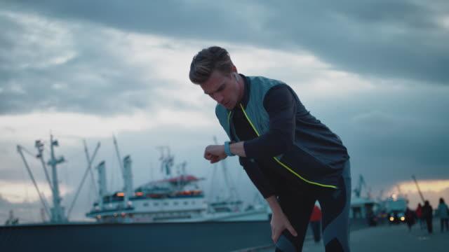vídeos y material grabado en eventos de stock de joven corriendo y mirando el rastreador de fitness - cansado