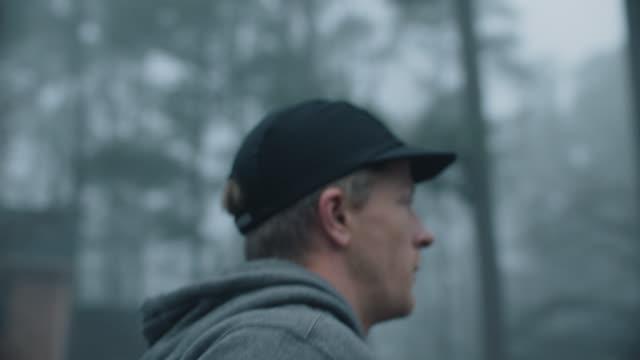 slo mo cu young man jogging at dawn turns down side street - sweatshirt stock videos & royalty-free footage