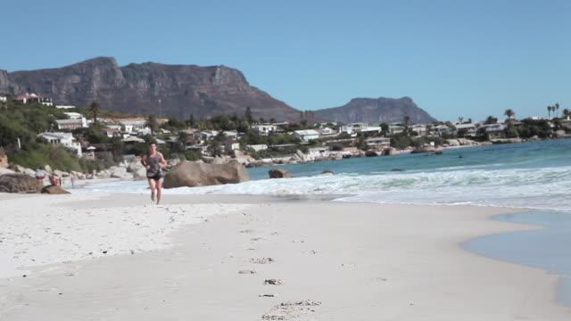 stockvideo's en b-roll-footage met young man jogging on beach - gymbroek