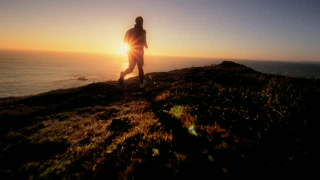 Young man jogging trail overlooking Pacific Ocean at sunset