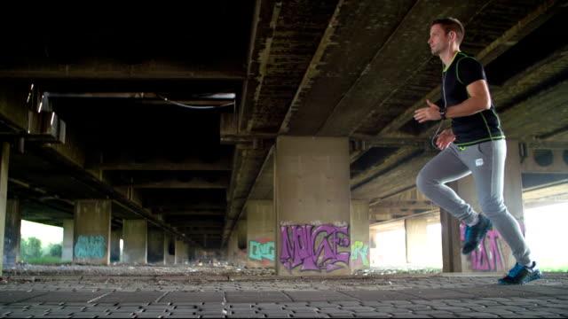 SLOWMO: Young Man Jogging Under The Bridge.