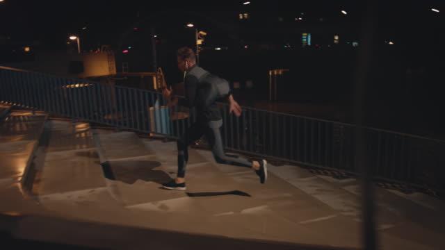 vídeos de stock, filmes e b-roll de homem novo que movimenta-se acima e para baixo em etapas na noite - vista lateral