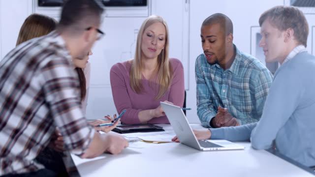 Junger Mann bei einem meeting mit Kollegen zu beginnen