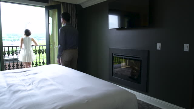 young man joining a young woman on balcony of their hotel room - viewpoint stock videos & royalty-free footage
