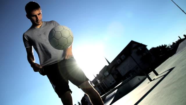 HD SUPER SLOW-MO: Young Man Juggling A Football