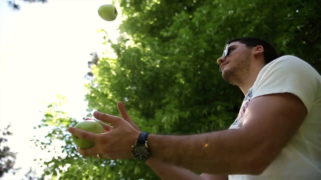 young man juggling with green apples - juggling stock videos & royalty-free footage