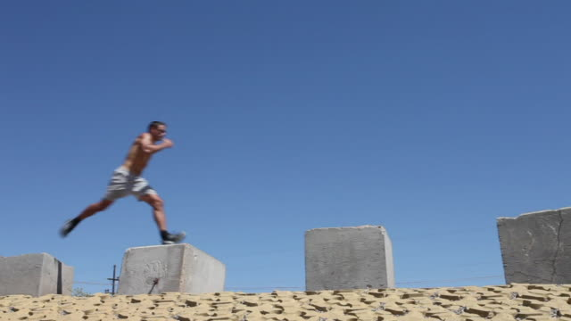 WS PAN Young man jumping across rocks / Santa Fe, New Mexico, USA