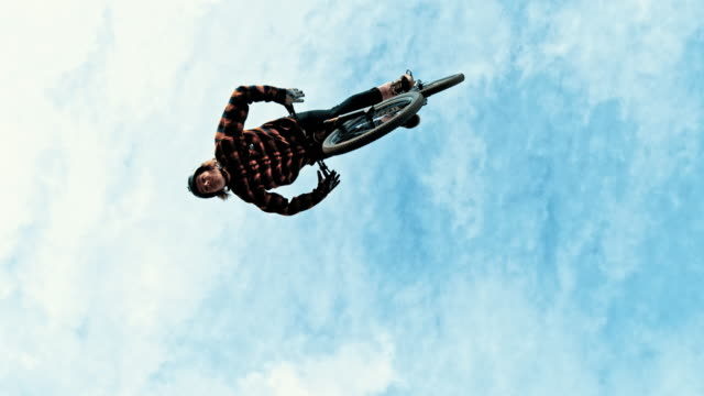 ms young man jumping and backflipping bmx bicycle against blue sky with clouds - acrobatic activity stock videos and b-roll footage