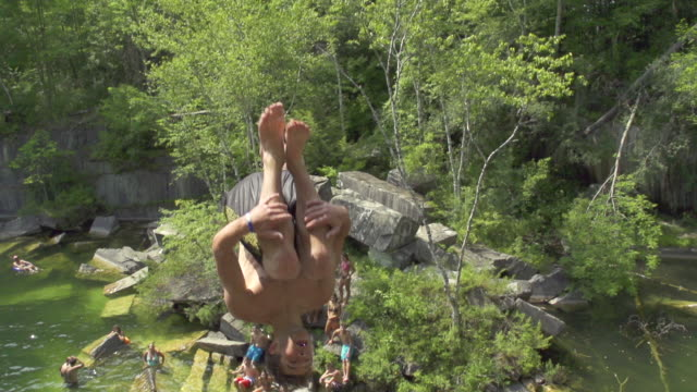 MS TD TS SLO MO Young man jumping and fliping over cliff into water / Dorset, Vermont, United States
