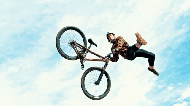 ms young man jumping and spinning bmx bicycle against cloudy sky - exhilaration stock videos & royalty-free footage