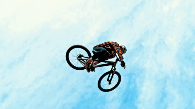 MS Young man jumping BMX bicycle against blue sky and clouds