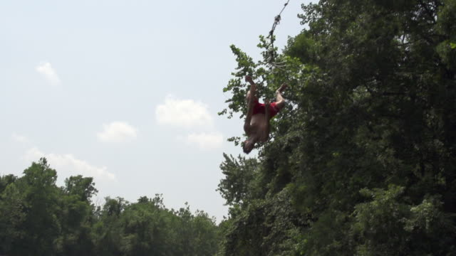 ms ts slo mo young man jumping from high tree position with rope swing and somersaulting in river / farmington, connecticut, united states - rope swing stock videos & royalty-free footage