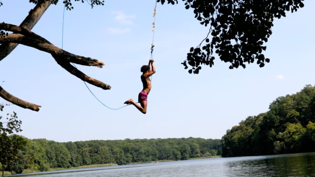 young man jumping from rope swing into lake - rope swing stock videos & royalty-free footage