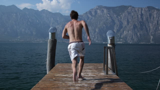 Young man jumping in lake