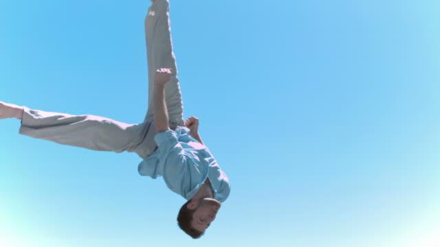 stockvideo's en b-roll-footage met man jumping in slow motion on a trampoline - trampoline
