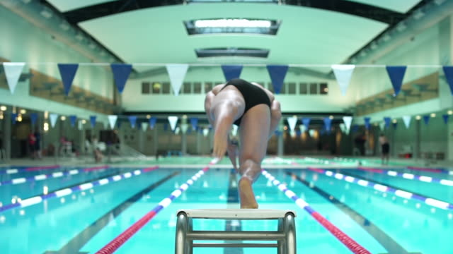 young man jumping into a swimming pool - swimming pool stock videos & royalty-free footage