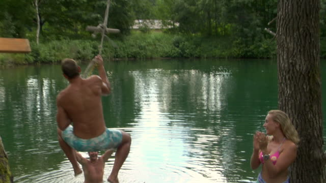slo mo ms young man jumping into lake, man and woman applauding, bavaria, germany - see stock-videos und b-roll-filmmaterial