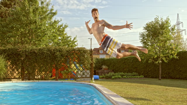 slo mo ts young man jumping into the pool - lawn stock videos & royalty-free footage