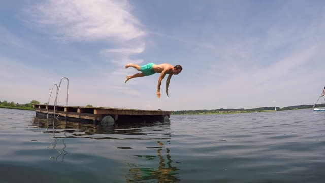 Young man jumping into the water from a wooden pontoon. Slow motion