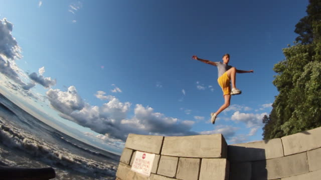 A young man jumping off a wall during sunset at the beach. - Model Released - HD