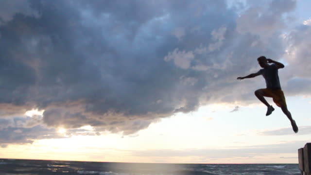 vidéos et rushes de a young man jumping off a wall during sunset at the beach. - model released - hd - sauter