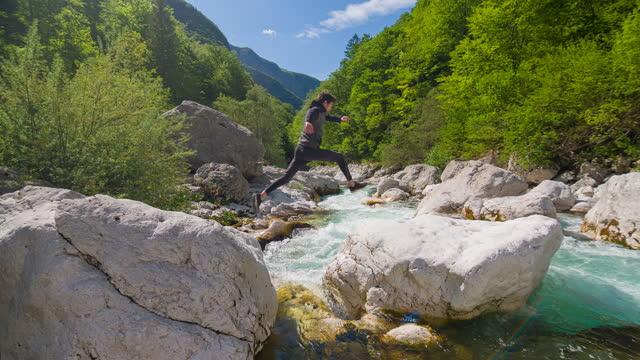junger mann springt in majestätischer landschaft über den bergfluss - überqueren stock-videos und b-roll-filmmaterial