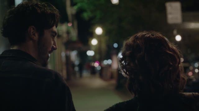 MS SLO MO. Young man kisses girlfriend as they walk hand in hand down city sidewalk at night.