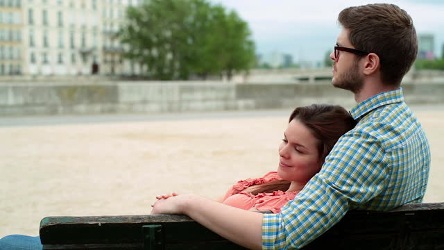 young man kisses his girlfriend on the forehead as she rests in his arms on romantic date in paris. - coppia di giovani video stock e b–roll