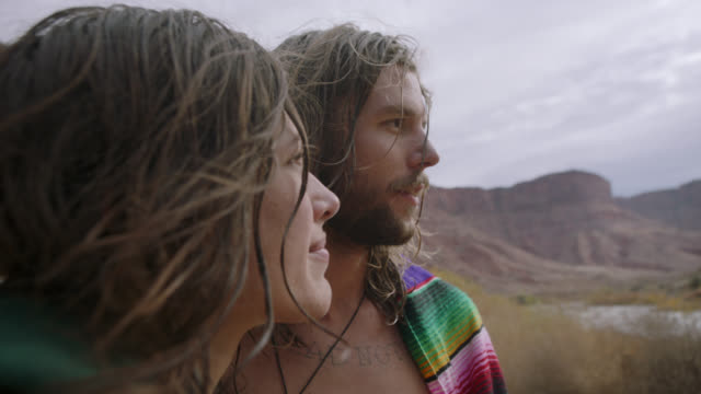 SLO MO. Young man kisses woman and she looks up at him and smiles as they stand by Colorado River on Moab camping trip.