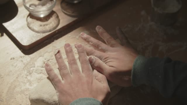 stockvideo's en b-roll-footage met cu young man kneading dough at home - broodje voedsel