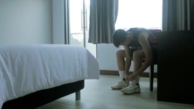 vídeos y material grabado en eventos de stock de young man lacing his shoes wide shot - un solo adolescente
