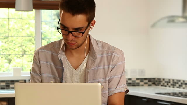 Young man, laptop, glasses, kitchen.