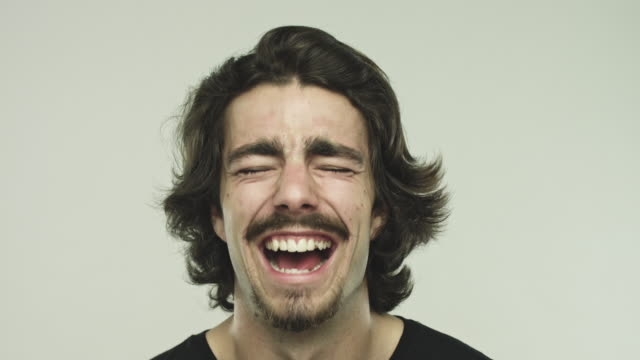 Hombre joven riendo sobre fondo gris