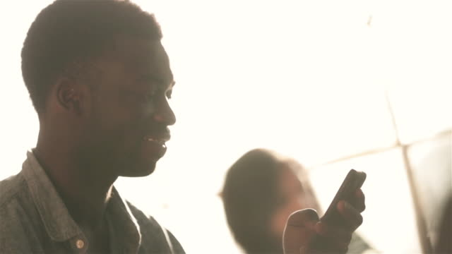 Young man laughs and shakes head at smartphone