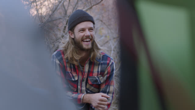 vidéos et rushes de young man laughs with friends on camping trip. - bûcheron