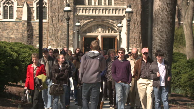 vidéos et rushes de ms cu young man leading group of people on tour through university campus, bethlehem, pennsylvania, usa - hommes d'âge moyen