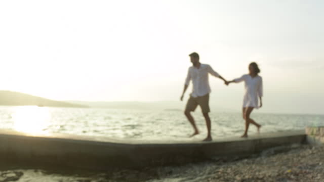young man leads a woman by the hand walking along a jetty by the sea and they stop to kiss. - ブラック島点の映像素材/bロール