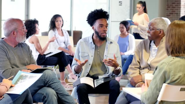 young man leads multi-ethnic discussion group - brochure stock videos & royalty-free footage