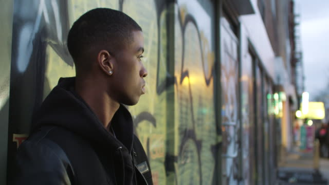 Young man leans agains wall with graffiti in the evening