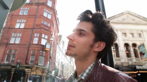 vídeos de stock, filmes e b-roll de young man leans on post and smokes cigarette on london street corner. - charuto