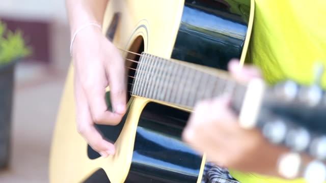 Junger Mann lernen, spielen Sie Gitarre