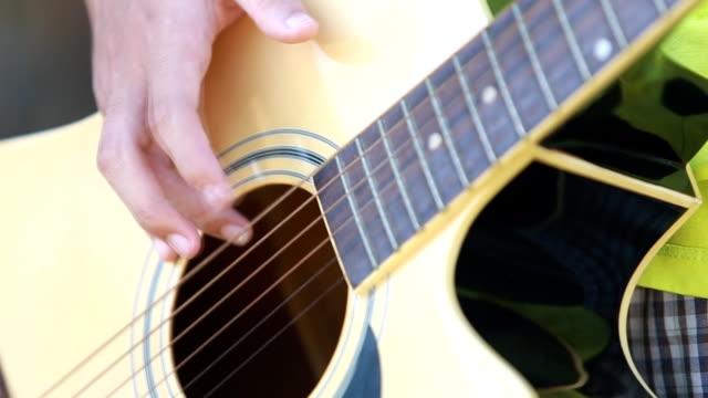 vidéos et rushes de jeune homme jouer de la guitare en savoir - doigt humain